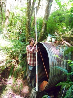 Fish passage barrier assessment intern measuring a culvert.
